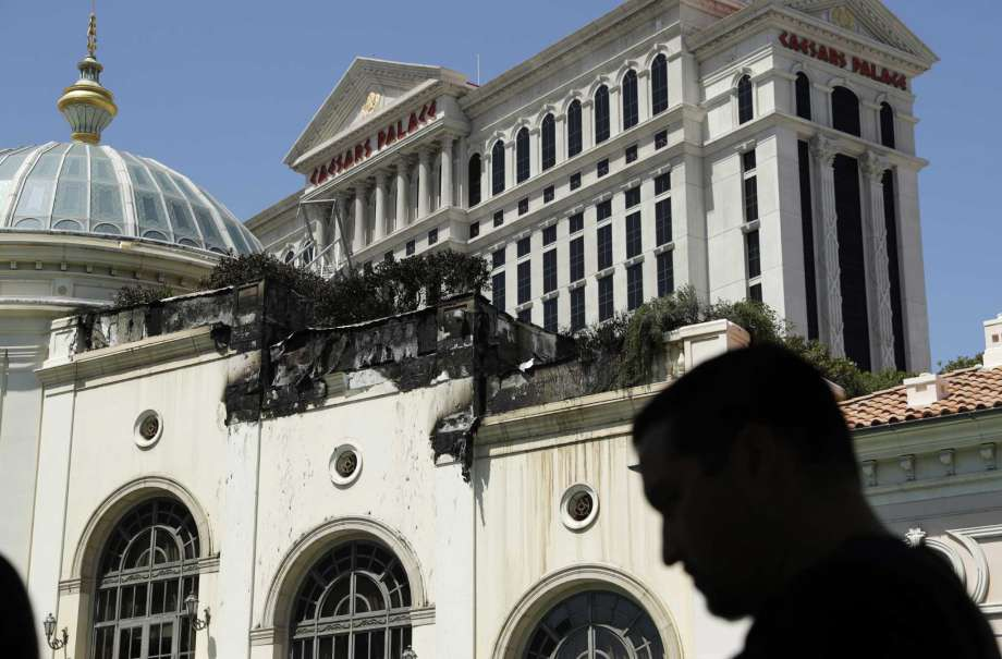 People look at fire damage at the Bellagio casino and resort, Friday, April  14